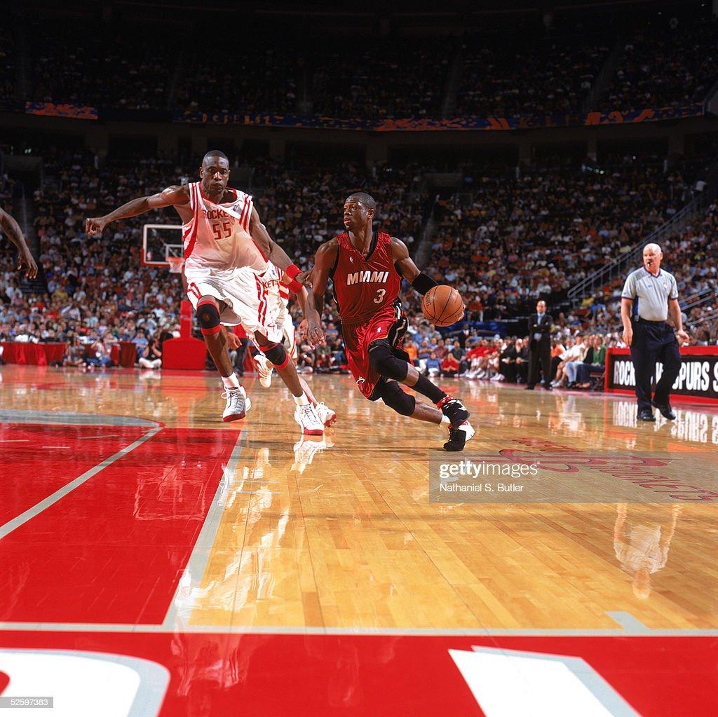 Dwyane Wade of the Miami Heat drives past Dikembe Mutombo of the ...