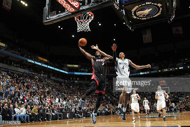 Dwyane Wade of the Miami Heat dunks against Wesley Johnson of the Minnesota Timberwolves during the game on April 1 2011 at Target Center in...