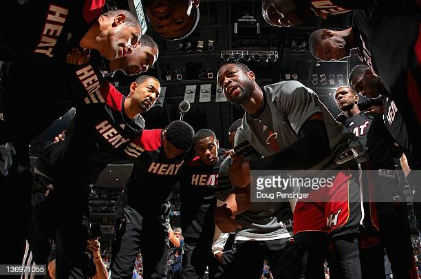 Dwyane Wade of the Miami Heat encourages his teammates at the center of the huddle as they prepare to face the Denver Nuggets at the Pepsi Center on...