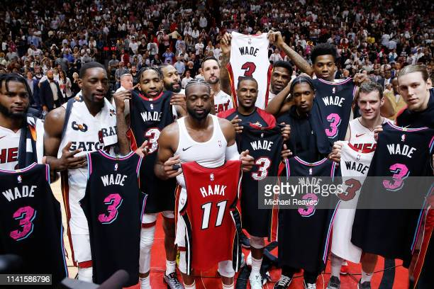 Dwyane Wade of the Miami Heat exchanges jerseys with the entire Miami Heat team after the final regular season home game of his career at American...