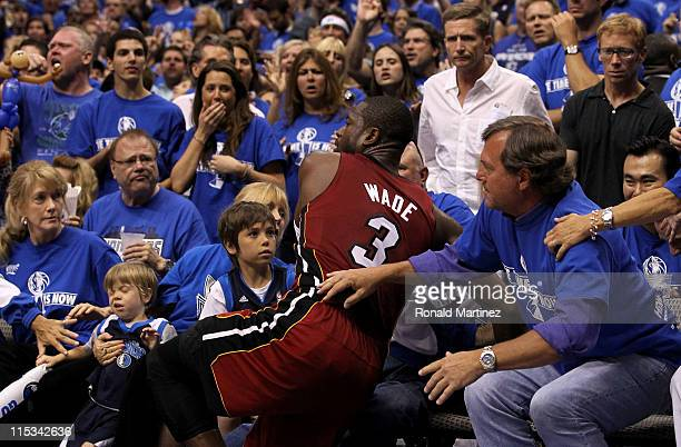 Dwyane Wade of the Miami Heat falls into fans sitting courtside after fouling Jason Kidd of the Dallas Mavericks in the first half of Game Three of...