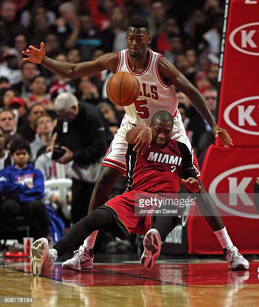 Dwyane Wade of the Miami Heat gets off a pass as he slips and falls into Bobby Portis of the Chicago Bulls at the United Center on January 25 2016 in...