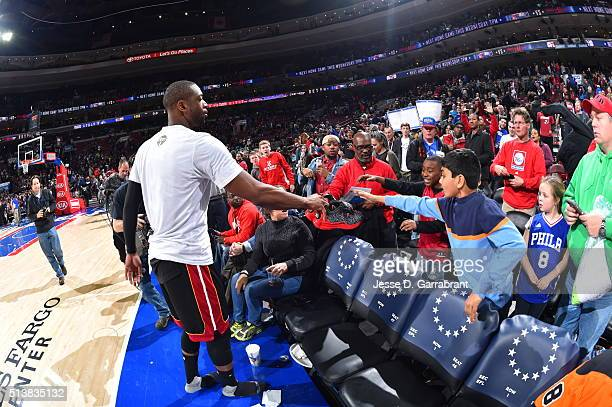 Dwyane Wade of the Miami Heat gives his game used sneakers to young fans against the Philadelphia 76ers at Wells Fargo Center on March 4 2016 in...