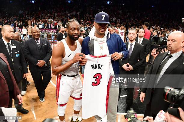 Dwyane Wade of the Miami Heat gives his jersey to former NBA player Carmelo Anthony after the game against the Brooklyn Nets at Barclays Center on...