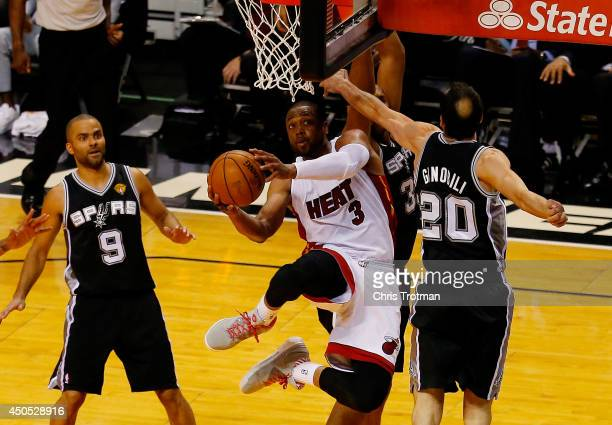 Dwyane Wade of the Miami Heat goes to the basket against Manu Ginobili of the San Antonio Spurs during Game Four of the 2014 NBA Finals at American...