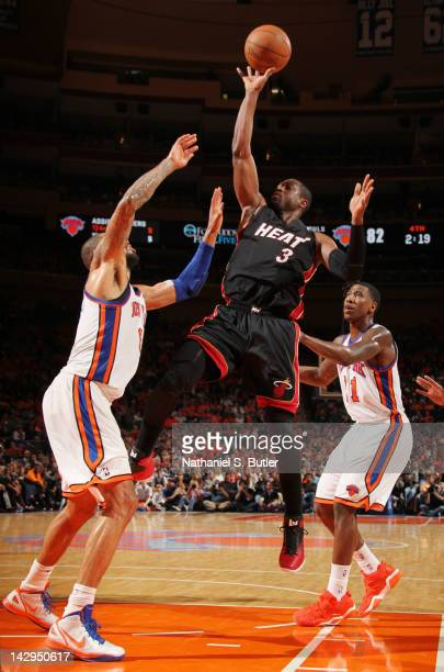 Dwyane Wade of the Miami Heat goes to the basket against Tyson Chandler and Iman Shumpert of the New York Knicks on April 15 2012 at Madison Square...