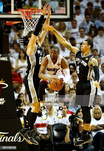 Dwyane Wade of the Miami Heat goes to the basket as Tiago Splitter and Danny Green of the San Antonio Spurs defend during Game Three of the 2014 NBA...