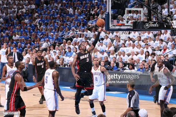 Dwyane Wade of the Miami Heat goes to the basket between Kendrick Perkins Thabo Sefolosha and Serge Ibaka of the Oklahoma City Thunder during Game...