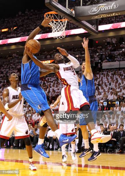 Dwyane Wade of the Miami Heat goes up for a shot between Brendan Haywood and Peja Stojakovic of the Dallas Mavericks in the first half in Game One of...