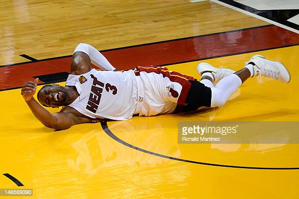 Dwyane Wade of the Miami Heat grabs his back as he lies on the court in pain in the second quarter against the Oklahoma City Thunder in Game Four of...
