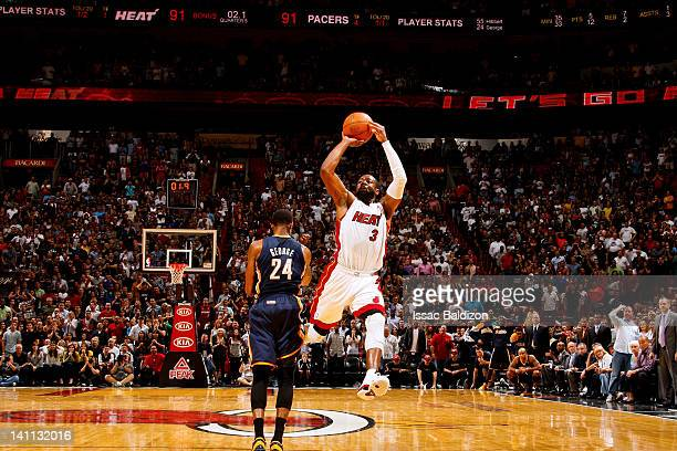 Dwyane Wade of the Miami Heat hits the winning shot in overtime against Paul George of the Indiana Pacers on March 10 2012 at American Airlines Arena...