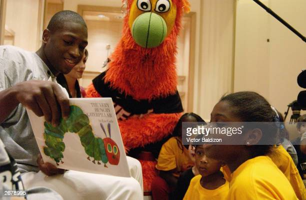 Dwyane Wade of the Miami Heat holds a book as a child reads while mascot Burnie watches during the Read to Achieve event at Saks Fifth Avenue on...