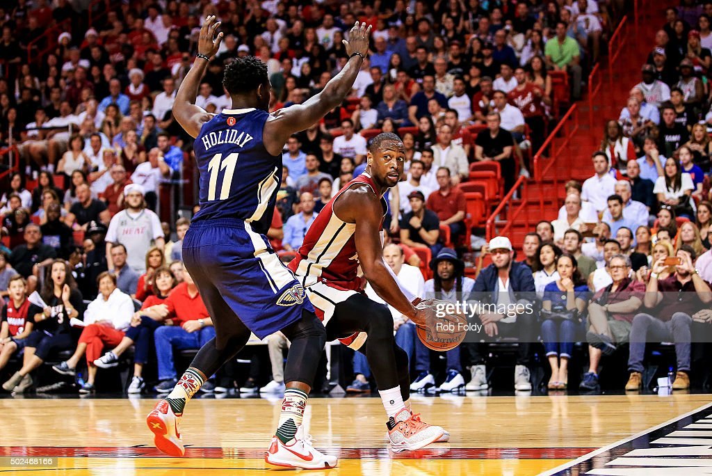 Dwyane Wade #3 of the Miami Heat is defended by Jrue Holiday #11 of the New Orleans Pelicans during the game at American Airlines Arena on December 25, 2015 in Miami, Florida.