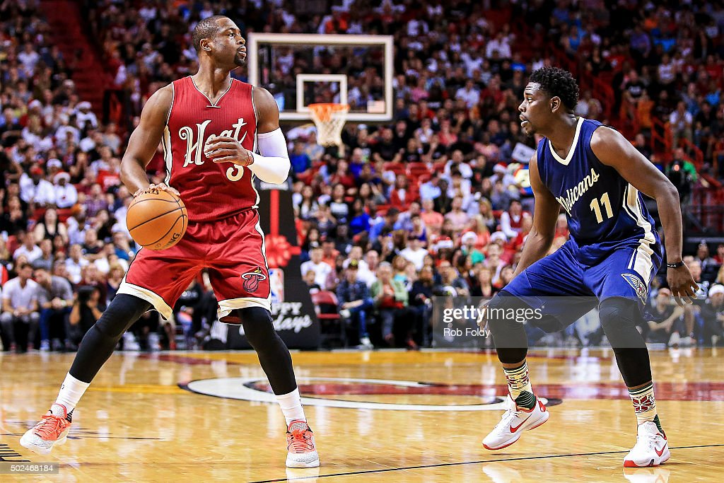 Dwyane Wade #3 of the Miami Heat is defended by Jrue Holiday #11 of the New Orleans Pelicans during the second half of the game at American Airlines Arena on December 25, 2015 in Miami, Florida.
