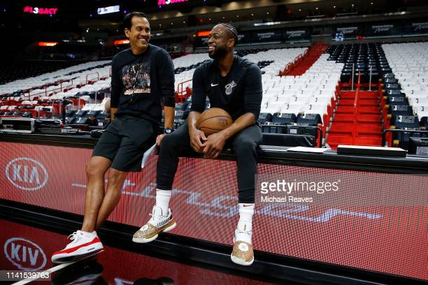 Dwyane Wade of the Miami Heat laughs with head coach Erik Spoelstra prior to his final regular season home game of his career against the...