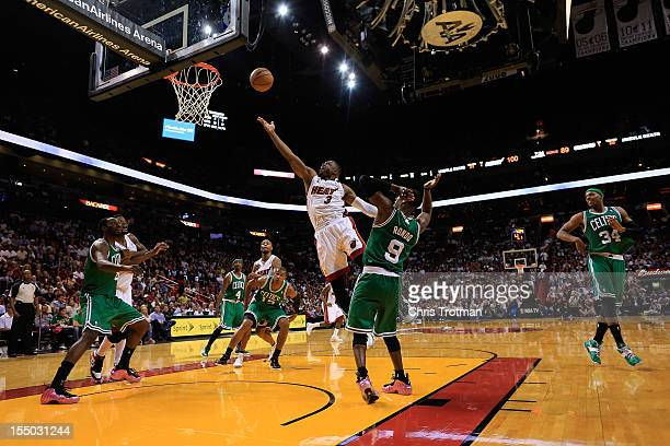 Dwyane Wade of the Miami Heat lays the ball up over Rajon Rondo of the Boston Celtics at American Airlines Arena on October 30 2012 in Miami Florida...