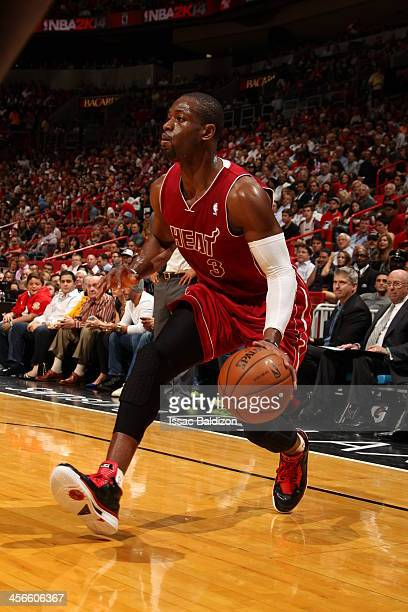 Dwyane Wade of the Miami Heat looks to pass the ball against the Cleveland Cavaliers on December 14 2013 at American Airlines Arena in Miami Florida...