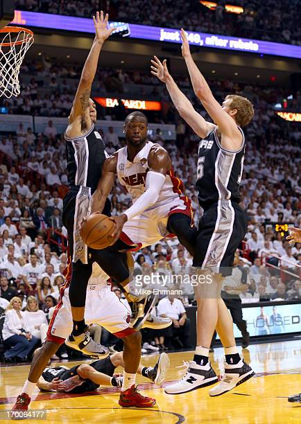 Dwyane Wade of the Miami Heat looks to pass the ball between Danny Green and Matt Bonner of the San Antonio Spurs in the second quarter during Game...