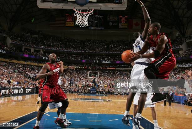 Dwyane Wade of the Miami Heat looks to pass the ball to Shaquille O'Neal around DeSagana Diop of the Dallas Mavericks during Game Six of the 2006 NBA...