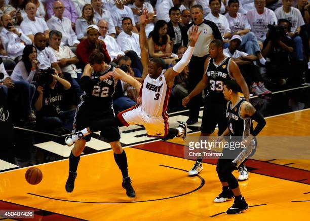 Dwyane Wade of the Miami Heat loses the ball as Tiago Splitter of the San Antonio Spurs defends during Game Three of the 2014 NBA Finals at American...