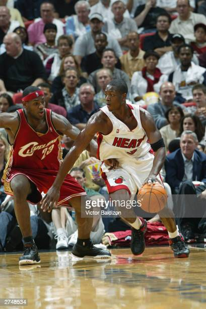 Dwyane Wade of the Miami Heat moves the ball as LeBron James of the Cleveland Cavaliers covers him during the game on November 12 2003 at American...