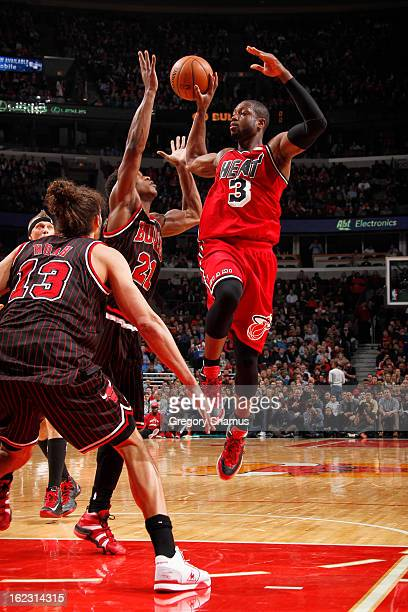 Dwyane Wade of the Miami Heat nolook passes the ball against Jimmy Butler and Joakim Noah of the Chicago Bulls on February 21 2013 at the United...