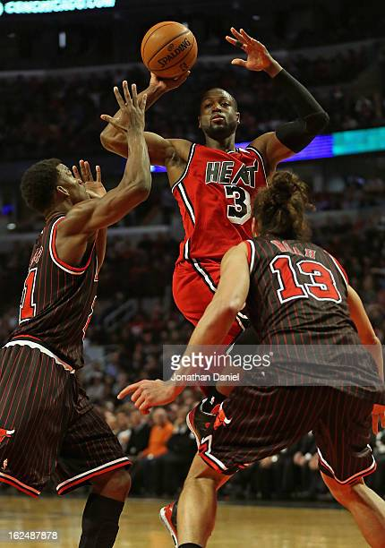Dwyane Wade of the Miami Heat passes over Jimmy Butler and Joakim Noah of the Chicago Bulls at the United Center on February 21 2013 in Chicago...
