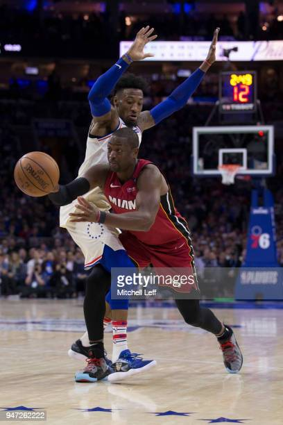 Dwyane Wade of the Miami Heat passes the ball around Robert Covington of the Philadelphia 76ers in the third quarter during Game Two of the first...