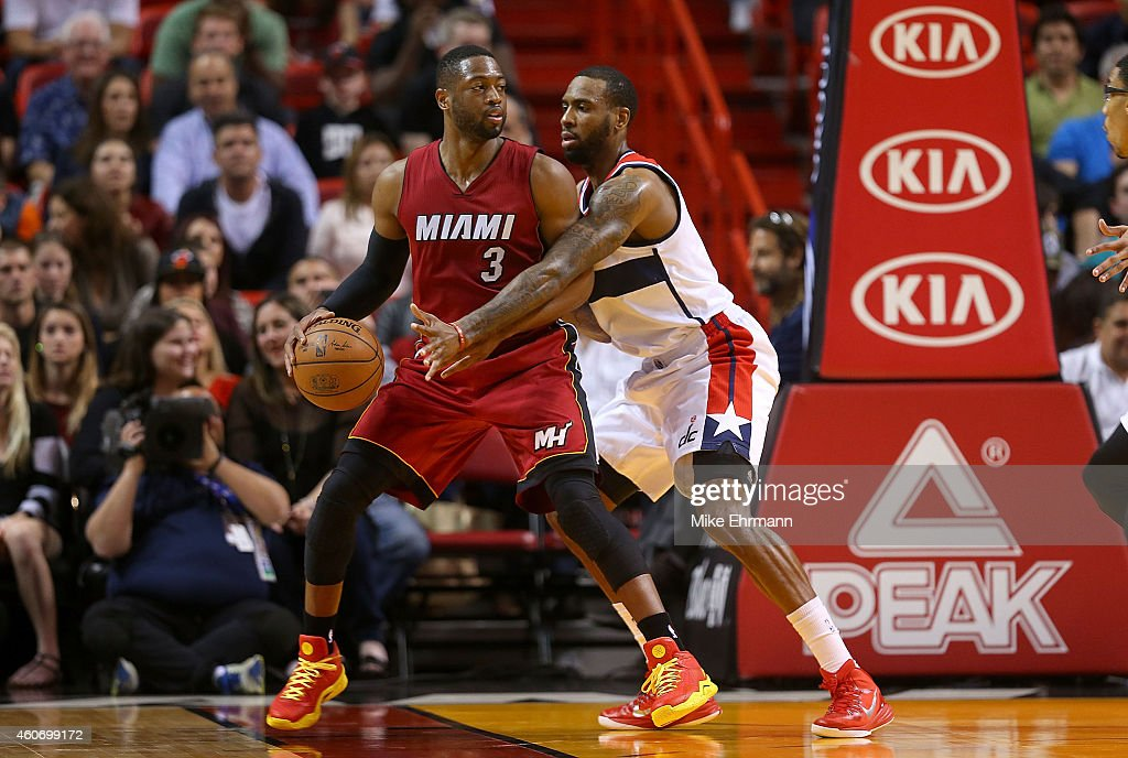 Dwyane Wade #3 of the Miami Heat posts up Garrett Temple #17 of the Washington Wizards during a game at American Airlines Arena on December 19, 2014 in Miami, Florida.
