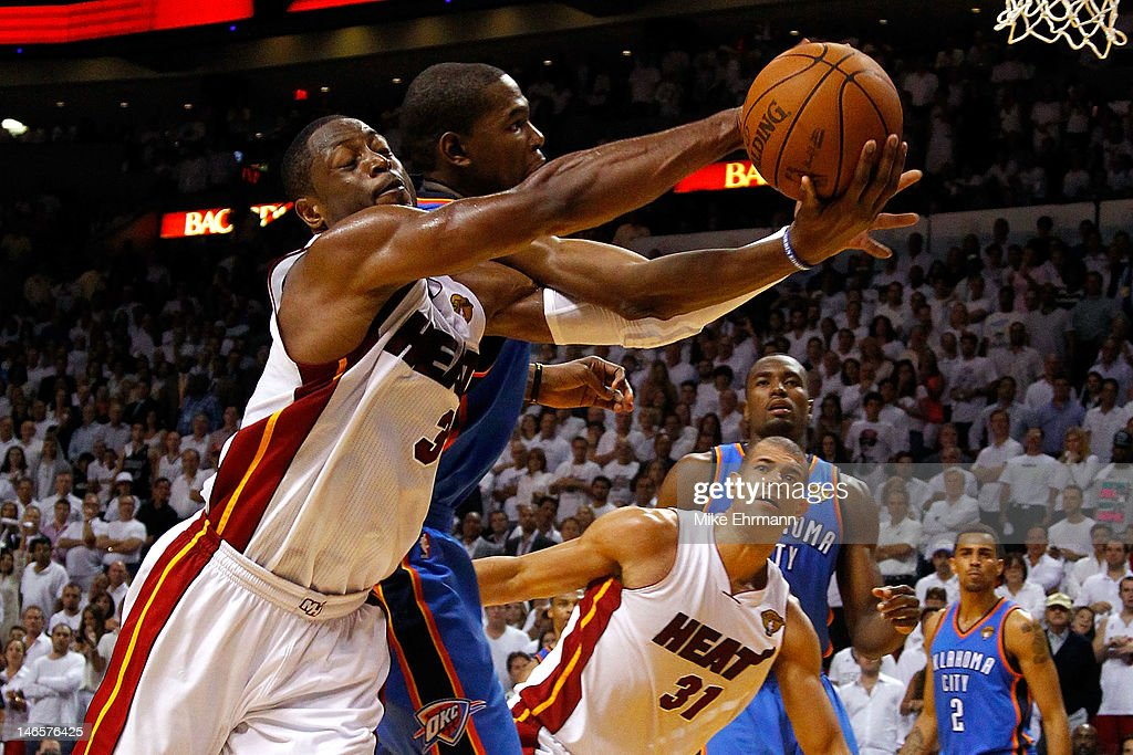 Dwyane Wade #3 of the Miami Heat reaches to save the ball from going out of bounds in the fourth quarter against Kevin Durant #35 of the Oklahoma City Thunder in Game Four of the 2012 NBA Finals on June 19, 2012 at American Airlines Arena in Miami, Florida. The Heat won 104-98.