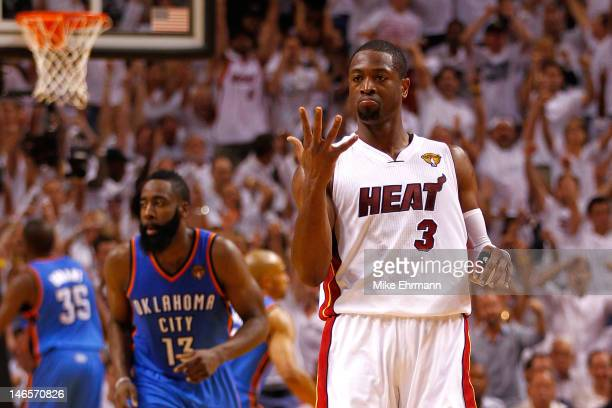 Dwyane Wade of the Miami Heat reacts after he made a 3-point basket in the second half against James Harden of the Oklahoma City Thunder in Game Four...