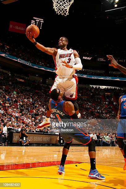 Dwyane Wade of the Miami Heat shoots against Amar'e Stoudemire of the New York Knicks on February 27 2011 at American Airlines Arena in Miami Florida...