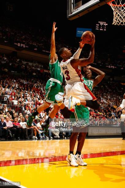Dwyane Wade of the Miami Heat shoots against Courtney Lee and Brandon Bass of the Boston Celtics during a game on October 30 2012 at American...