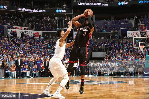 Dwyane Wade of the Miami Heat shoots against Courtney Lee of the Charlotte Hornets in Game Six of the Eastern Conference Quarterfinals during the...