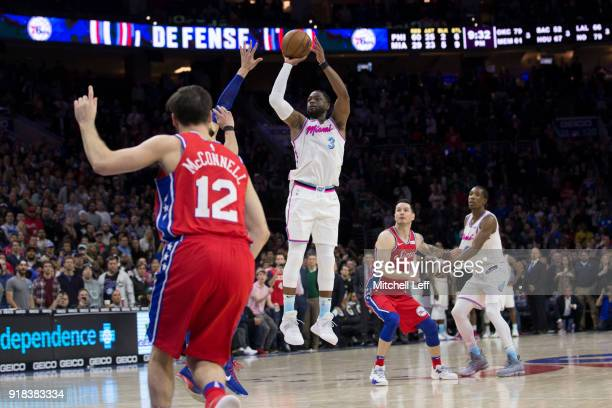 Dwyane Wade of the Miami Heat shoots and misses a goahead threepoint shot as TJ McConnell and JJ Redick of the Philadelphia 76ers look on in the...