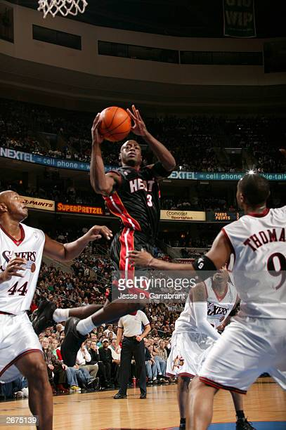 Dwyane Wade of the Miami Heat shoots between Kenny Thomas and Derrick Coleman of the Philadelphia 76ers during a NBA game October 28 2003 at the...