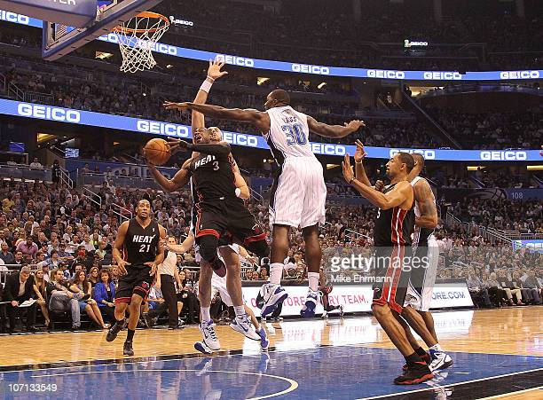 Dwyane Wade of the Miami Heat shoots over Brandon Bass of the Orlando Magic during a game at Amway Arena on November 24 2010 in Orlando Florida NOTE...