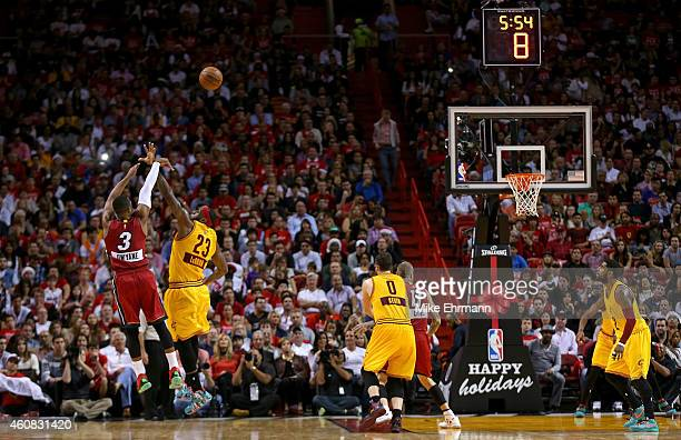 Dwyane Wade of the Miami Heat shoots over LeBron James of the Cleveland Cavaliers during a game at American Airlines Arena on December 25 2014 in...