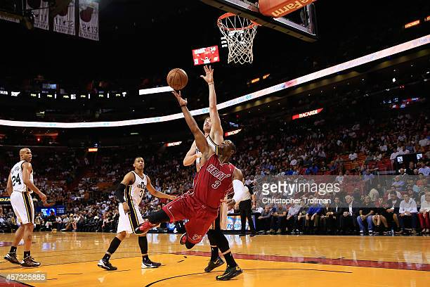 Dwyane Wade of the Miami Heat shoots the ball under pressure from Gordon Hayward of the Utah Jazz at American Airlines Arena on December 16 2013 in...
