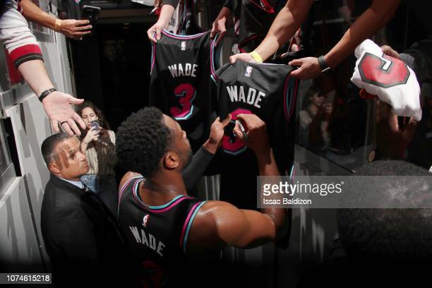Dwyane Wade of the Miami Heat signs autographs for fans after a game against the Milwaukee Bucks on December 22 2018 at American Airlines Arena in...