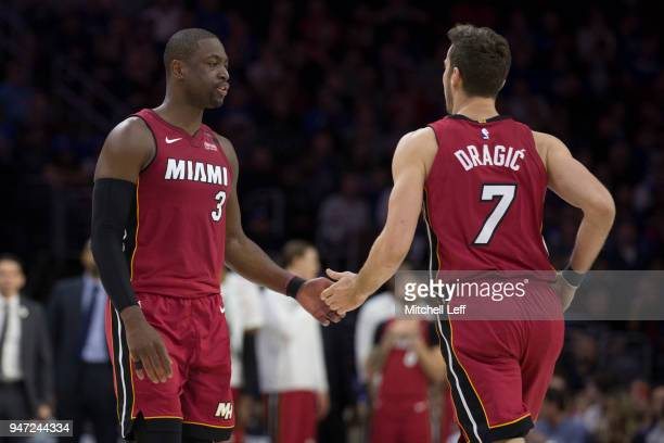 Dwyane Wade of the Miami Heat slaps hands with Goran Dragic in the second quarter against the Philadelphia 76ers during Game Two of the first round...