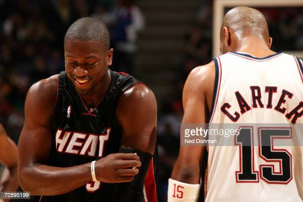 Dwyane Wade of the Miami Heat smiles near Vince Carter of the New Jersey Nets on November 10 2006 at the Continental Airlines Arena in East...