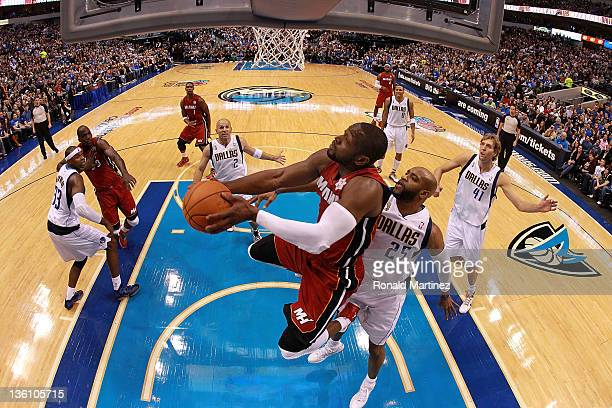 Dwyane Wade of the Miami Heat takes a shot against Vince Carter of the Dallas Mavericks during the NBA season opening game at American Airlines...