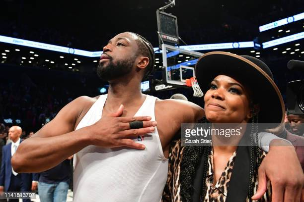 Dwyane Wade of the Miami Heat thanks the fans with his wife Gabrielle Union after the game against the Brooklyn Nets at Barclays Center on April 10,...