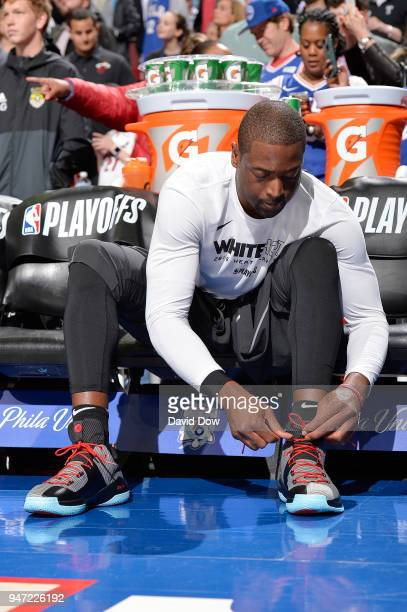 Dwyane Wade of the Miami Heat ties his sneakers before the game against the Philadelphia 76ers in Game Two of Round One of the 2018 NBA Playoffs on...