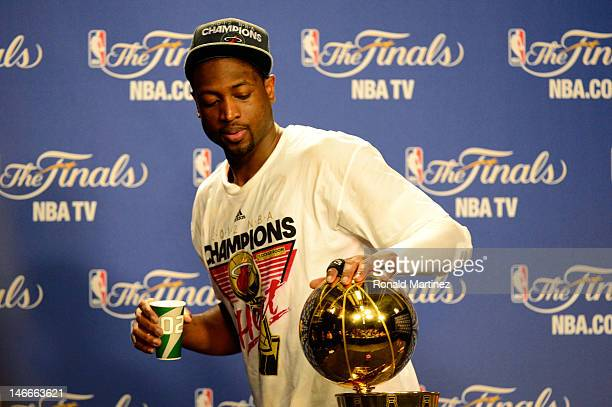 Dwyane Wade of the Miami Heat touches the Larry O'Brien Finals Championship trophy as he walsk out of his post game press conference after the Heat...