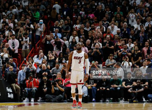 Dwyane Wade of the Miami Heat waves to the crowd during his final career regular season home game at American Airlines Arena against the Philadelphia...