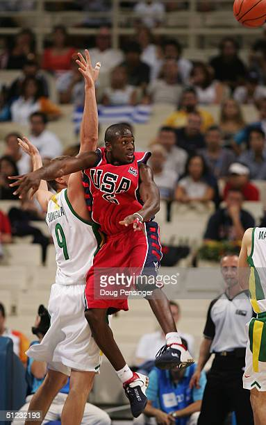 Dwyane Wade of the United States and Darius Songaila of Lithuania clash during the men's basketball bronze medal contest game on August 28 2004...