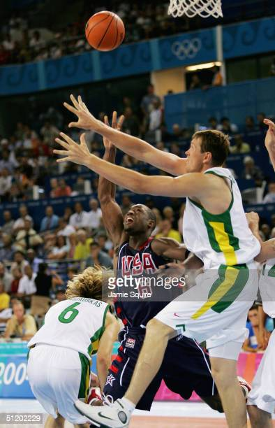 Dwyane Wade of the United States tries to throw the ball up over the defense of Darius Songaila and Arvydas Macijauskas of Lithuania in a men's...