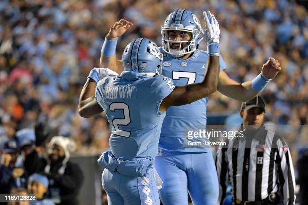 Dyami Brown celebrates with Sam Howell of the North Carolina Tar Heels after scoring a touchdown against the Virginia Cavaliers during the second...